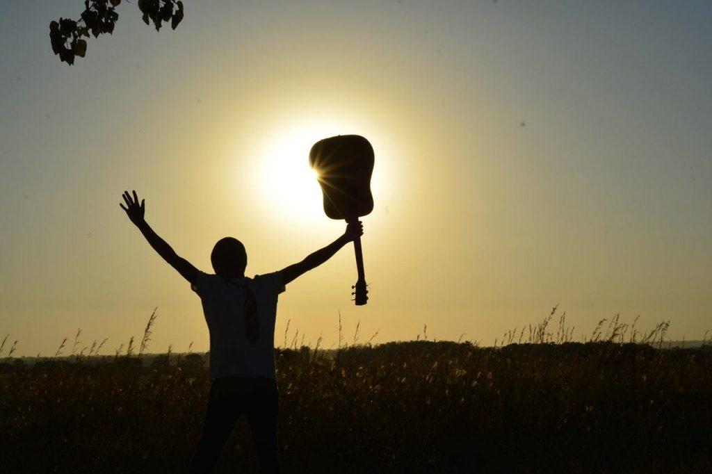 photo-homme-victorieux-guitare-coucher-de-soleil
