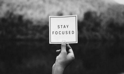 main-devant-paysage-qui-tien-étiquette-focus-motivation